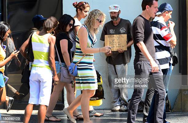 People walk past a homeless war veteran explaining his plight hoping for assistance while standing along Hollywood Boulevard in Hollywood California...