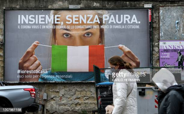People walk past a huge billboard that shows a woman with as protective mask in the colours of an Italian flag and which reads All together without...