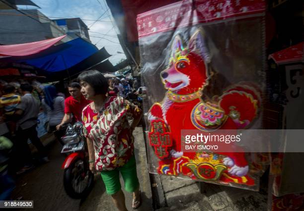 People walk past a kiosk selling Chinesestyle decorations for the Lunar New Year in Jakarta on February 16 2018 The 2018 Lunar New Year fell on...