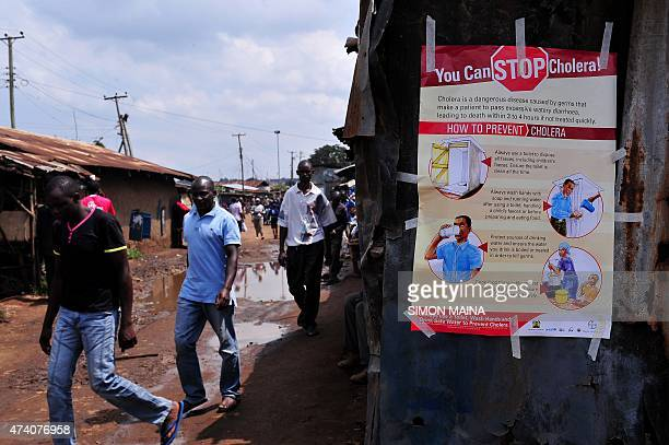 People walk past a kiosk where a poster giving information on how to prevent Cholera is displayed in the Kibera area of Nairobi on May 20 2015 At...