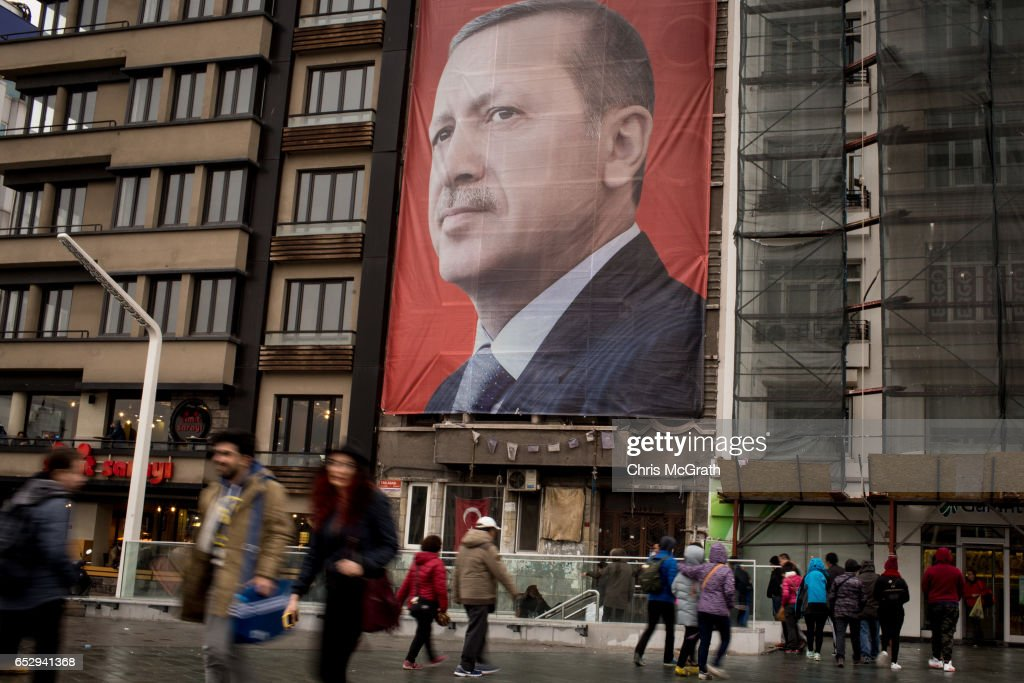 People walk past a large banner showing the portrait of Turkish President Recep Tayyip Erdogan in Taksim Square on March 13, 2017 in Istanbul, Turkey. Turkey will hold its constitutional referendum on April 16, 2017. Turks will vote on 18 proposed amendments to the Constitution of Turkey. The controversial changes seek to replace the parliamentary system and move to a presidential system which would give President Recep Tayyip Erdogan executive authority. Campaigning will officially begin on February 25 with a pro referendum rally to be held in Ankara and attended by Prime Minister Binali Yildirim.