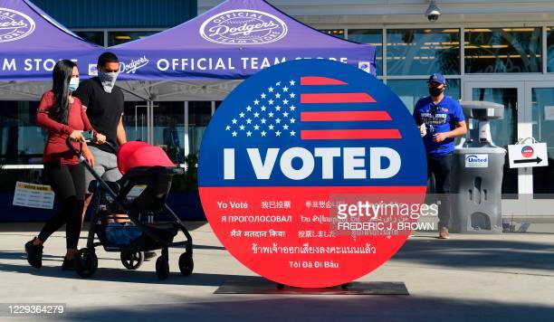 """People walk past a large """"I Voted"""" display as early voting for the election begins at Dodger Stadium in Los Angeles, California on October 30, 2020."""