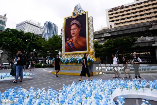 People walk past a large picture of Queen Sirikit at shopping in Bangkok Thailand on August 5 2017