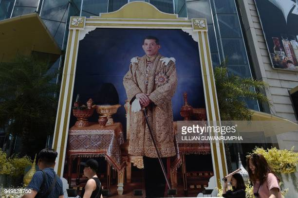 People walk past a large portrait of Thai King Maha Vajiralongkorn in Bangkok on April 22 2018