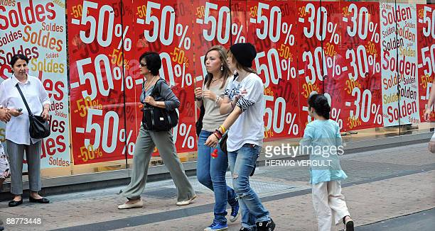 People walk past a large window with posters reading announcing price reductions, at the start of the summer sales period, in the 'Nieuwstraat - Rue...