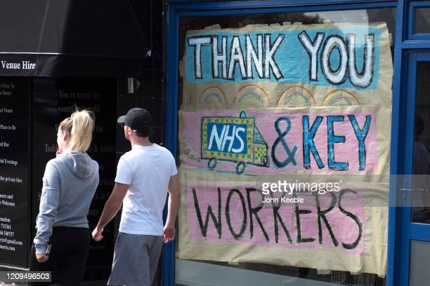 People walk past a local shop that has decorated its window thanking NHS and key workers on April 8, 2020 in Leigh on Sea, England. There have been...