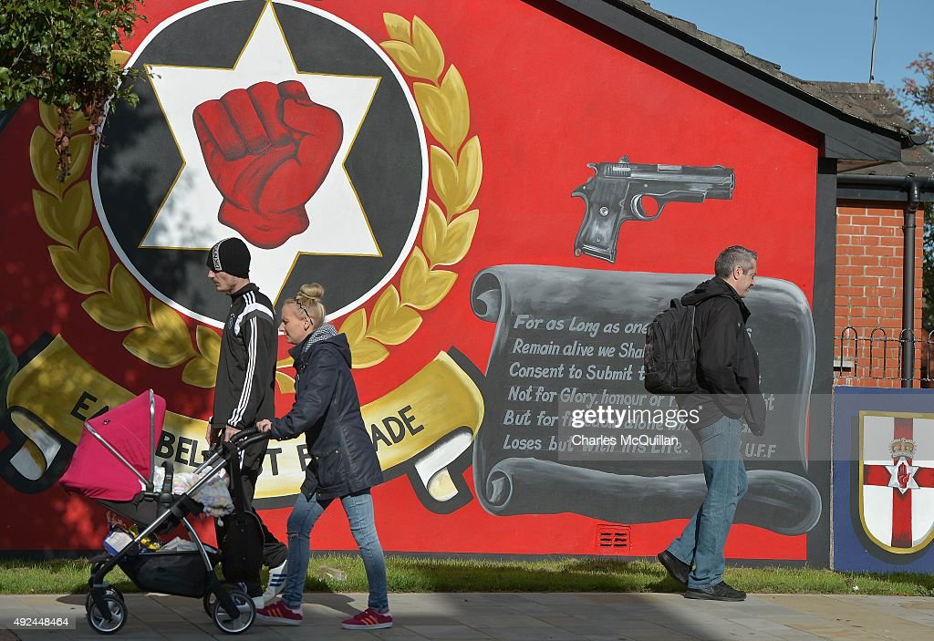 People walk past a loyalist paramilitary mural on the day that the new Loyalist Community Council was launched at the Park Avenue Hotel on October 13, 2015 in Belfast, Northern Ireland. The council has the backing of the three main loyalist paramilitary groups, the UVF, the UDA and the Red Hand Commandos. A joint statement from the three loyalist groups said that they are 're-committing to the principals of the Belfast Agreement' and that they 'eschew all violence and criminality'. The launch of the new loyalist community council comes against the backdrop of an ongoing crisis at Stormont following following allegations that the IRA were involved in the murder of their former member Kevin McGuigan.