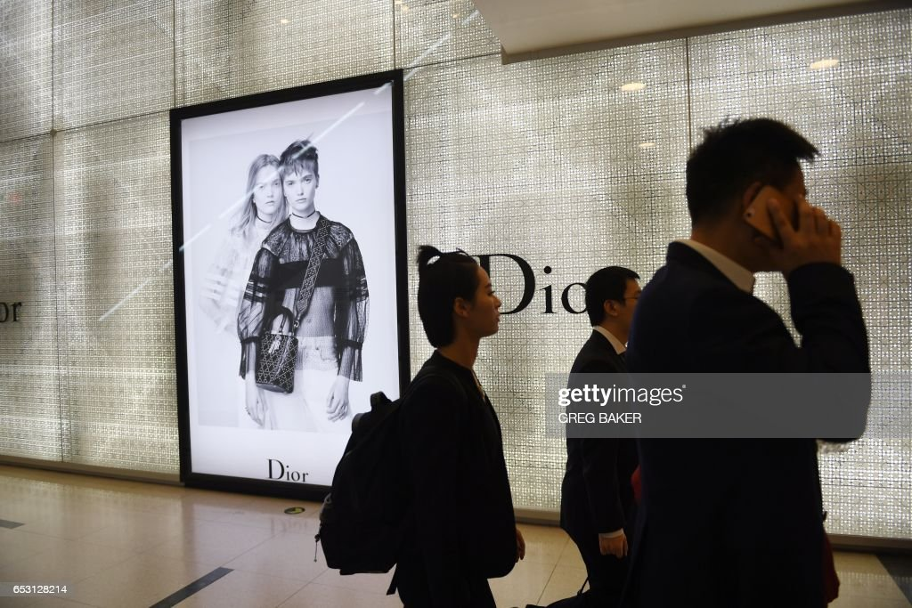 People walk past a luxury store in a shopping mall in Beijing on March 14, 2017. China retail sales growth decelerated to 9.5 percent year-on-year in January and February, government data showed on...
