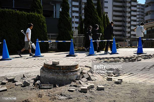 People walk past a manhole poking out from the ground due to the liquefaction triggered by the 90 magnitude earthquake on March 19 2011 in Urayasu...