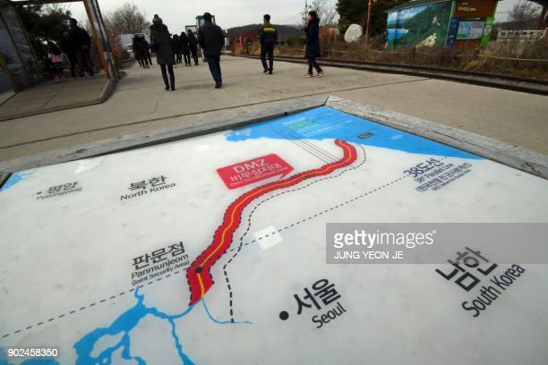 People walk past a map showing the Demilitarized Zone dividing the two Koreas at the Imjingak peace park at the border city of Paju on January 8 2018...