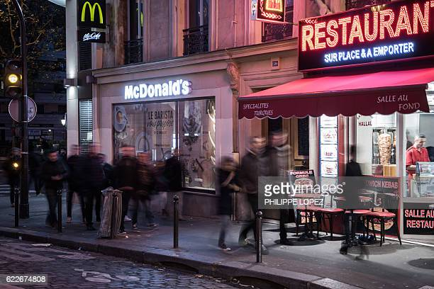People walk past a McDonald's restaurant near the Cafe Bonne Biere in Paris on November 11 a year after the Paris terror attacks / AFP / PHILIPPE...