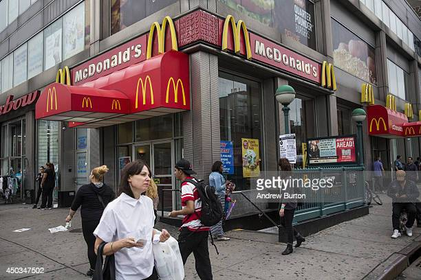 People walk past a McDonald's restaurant on June 9 2014 in New York City McDonald's domestic sales rose slightly in May but remain weak overall