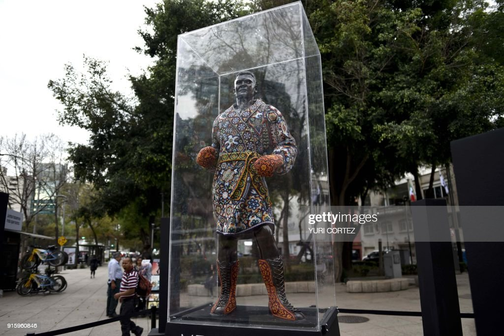 People walk past a monumental fiberglass sculpture of US boxer Muhammad Ali worked in Huichol art and placed along Reforma avenue as part of an exposition called 'the world's biggest Huichol exhibit', in Mexico City, on February 8, 2018. One hundred Wixarikas indigenous artists from the social and cultural company Paricuta made 10 monumental works of art inspired by sports and nature, which were put on public display on the street. /