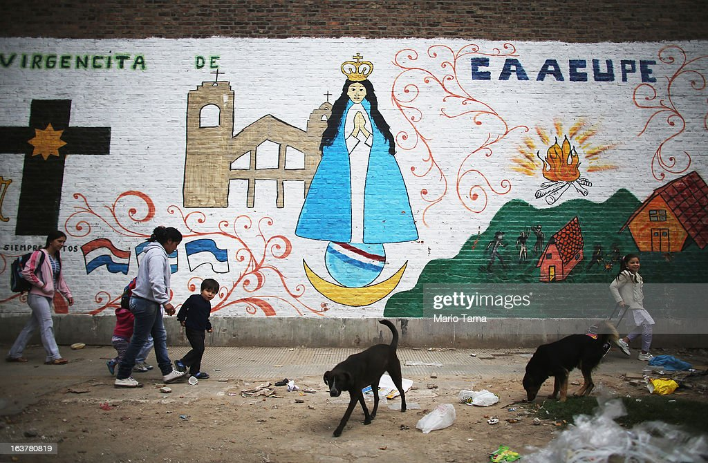 People walk past a mural as dogs scavenge near the Virgin of the Miracles of Caacupe church in the Villa 21-24 slum, where archbishop Jorge Mario Bergoglio, now Pope Francis, used to perform charity work, on March 15, 2013 in Buenos Aires, Argentina. Francis was the archbishop of Buenos Aires and is the first pope to hail from South America. Some locals are now affectionately calling Francis, known for his charity work in the slums, the 'slum pope.'