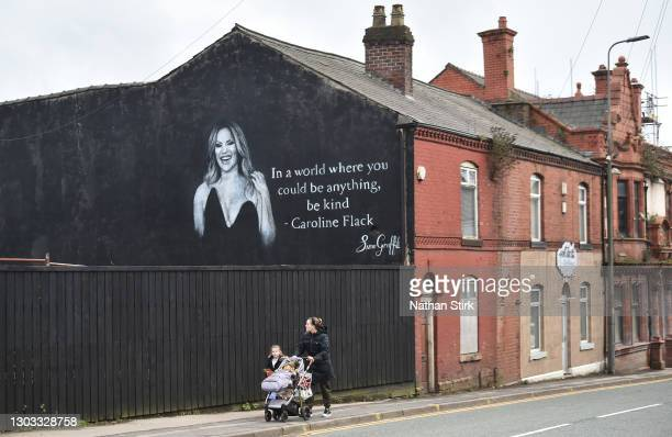 People walk past a mural by Artists Scott Wilcock which pays tribute to TV star Caroline Flack on February 21, 2021 in Wigan, England. Ms Flack, best...