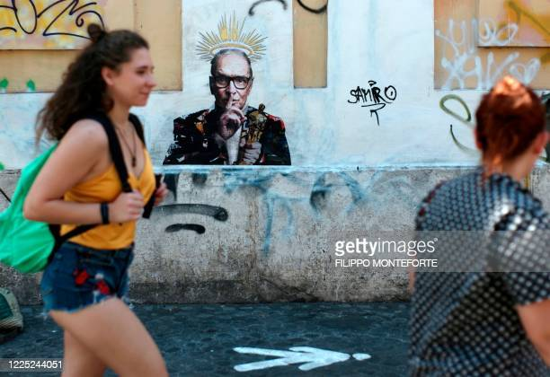 People walk past a mural by street artist Harry Greb depicting late Italian music composer Ennio Morricone, which has appeared in Rome a day after...