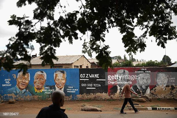 People walk past a mural depicting former South African President Nelson Mandela during different times in his life near the Regina Mundi Catholic...