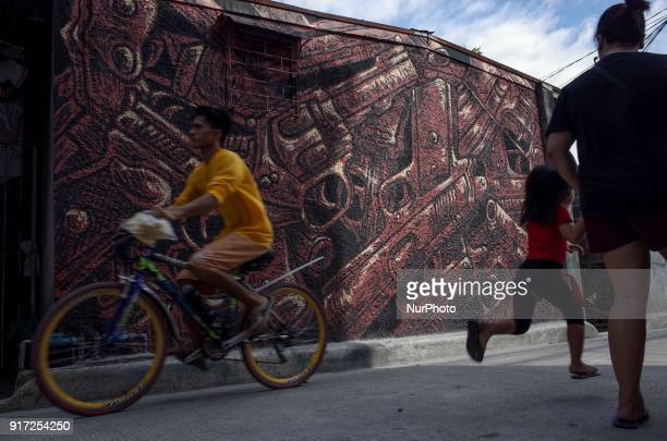 People walk past a mural depicting guns at a village in Manila Philippines on Monday February 12 2018 Philippine President Rodrigo Duterte announced...