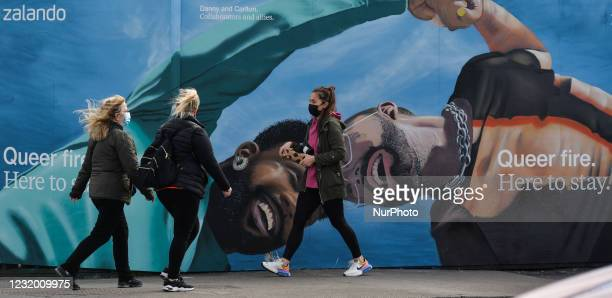 People walk past a mural for the Zalandos spring marketing campaign 'Here to Stay'. The campaign aims to foster a dialogue around core values, such...