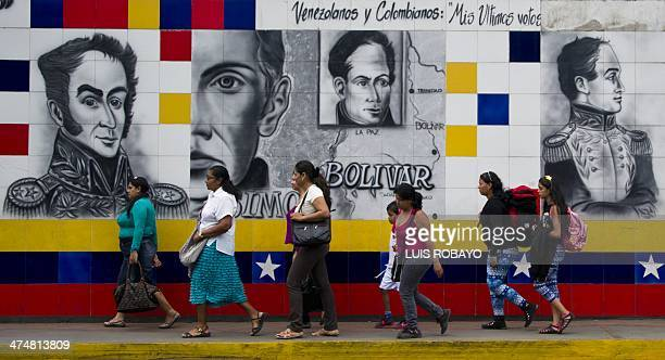 People walk past a mural of Venezuelan Liberator Simon Bolivar in San Antonio in the border state of Tachira Venezuela on February 25 2014 Angry...