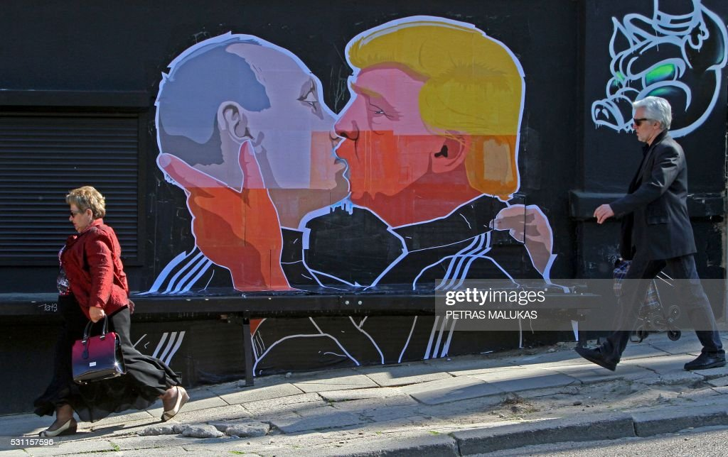TOPSHOT - People walk past a mural on a restaurant wall depicting US Presidential hopeful Donald Trump and Russian President Vladimir Putin greeting each other with a kiss in the Lithuanian capital Vilnius on May 13, 2016. Kestutis Girnius, associate professor of the Institute of International Relations and Political Science in Vilnius university, told AFP -This graffiti expresses the fear of some Lithuanians that Donald Trump is likely to kowtow to Vladimir Putin and be indifferent to Lithuanias security concerns. Trump has notoriously stated that Putin is a strong leader, and that NATO is obsolete and expensive. PHOTO / Petras Malukas