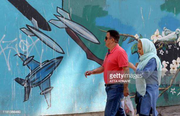 People walk past a mural painting along the wall of the former US embassy in the Iranian capital Tehran on June 22 2019 Fear of a potential war and...