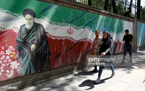 People walk past a mural painting showing the founder of the Islamic republic Ayatollah Ruhollah Khomeini and the national flag along the wall of the...
