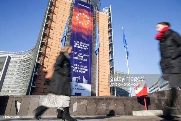 People walk past a new banner with the lettering reading 'For a union that strives for more' in different languages displayed on the facade of the...