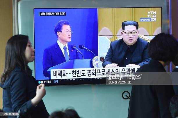 People walk past a news screen showing file footage of South Korean President Moon Jaein and North Korean leader Kim Jong Un at a railway station in...