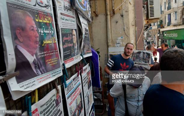 People walk past a newspaper stand showing the covers of national and foreign papers with the announced Algerian presidential election date...
