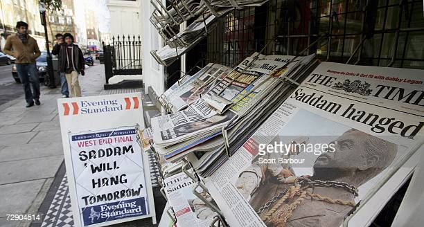People walk past a newstand displaying copies of newspapers with headlines of the death of former Iraqi president Saddam Hussein on December 30 2006...