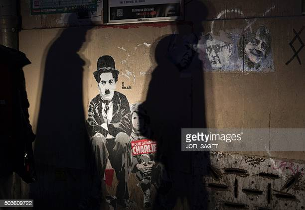 People walk past a paper mural by an unknown artist of British actor Charlie Chaplin with the lettering 'We are Charlie' and portraits of Charlie...