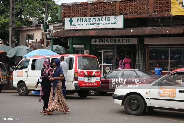 People walk past a pharmacy in Libreville on January 31 2018 The consumption of an emblematic painkiller often associated with alcohol is getting...