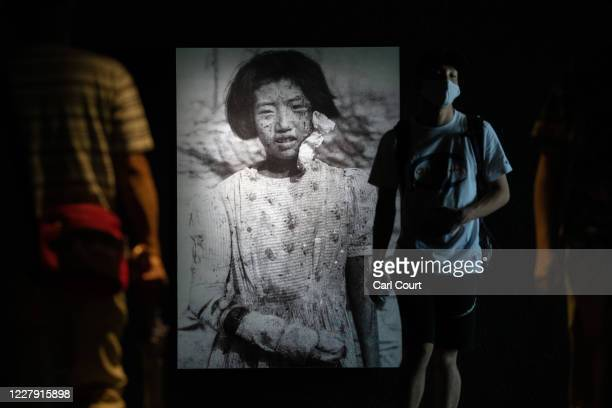 People walk past a photograph of 10-year-old atomic bomb survivor Yukiko Fujii who went on to have two children but died of cancer at the age of 42,...
