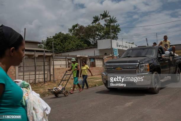 People walk past a pickup truck near the Venezuelan border in Pacaraima, Brazil, on Wednesday, April 10, 2019. Venezuelan refugees looking for work...