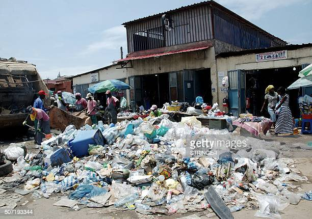 People walk past a pile of uncollected garbage in Luanda on January 20 2016 Since last summer Angola's sprawling capital of Luanda home to 65 million...