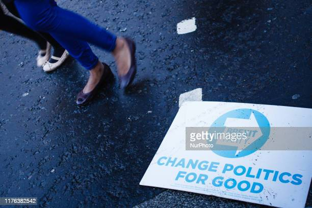 People walk past a placard for the Brexit Party lying in the road on Abingdon Street outside the Houses of Parliament in London England on October 17...