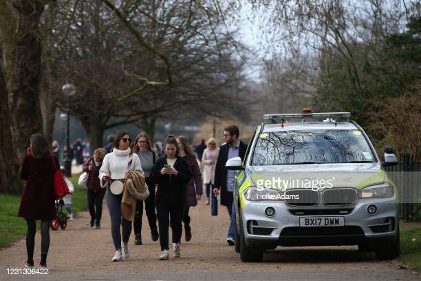 People walk past a police car parked at Hyde Park as on February 21, 2021 in London, England. The British government is expected to announce tomorrow...