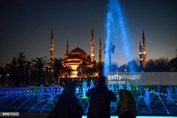 People walk past a pond as the Blue Mosque is seen in the backround on December 9 2017 during the evening at Sultanahmet district of Istanbul / AFP...