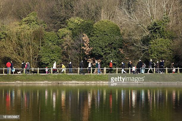 People walk past a pond on Hampstead Heath in North London on February 17 after the British captal awoke to unseasonably warm weather AFP PHOTO /...