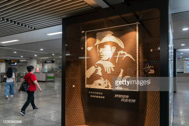 People walk past a portrait of singer Jay Chou, which is made up of Oreo Cookies, during an Oreo Art Exhibition at Xujiahui Subway Station on May 21,...