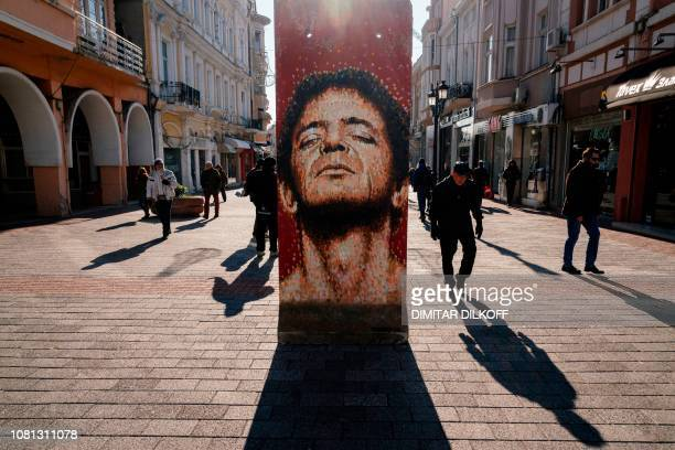 People walk past a portrait of US singer Lou Reed painted on a section of the Berlin Wall as part of the exhibition 'Art Liberty From the Berlin Wall...