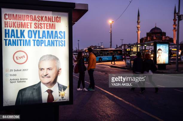 People walk past a poster advertising a rally of Turkish Prime Minister Binali Yildirim ahead of an upcoming constitutional referendum in the...