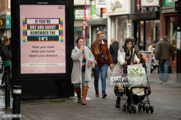 People walk past a poster advising shoppers of measures to combat the spread of the novel coronavirus pandemic, in the high street of Leigh, Greater...