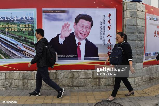 People walk past a poster featuring Chinese President Xi Jinping with a slogan reading 'Chinese Dream People's Dream' beside a road in Beijing on...