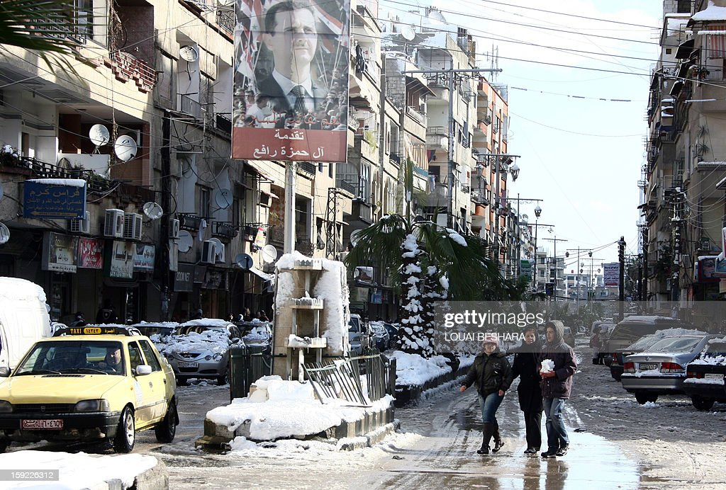 People walk past a poster featuring Syria's president in a street covered with snow on January 10, 2013 in the Syrian capital of Damascus. Snow carpeted Syria's war-torn cities but sparked no let-up in the fighting, instead heaping fresh misery on a civilian population already enduring a chronic shortage of heating fuel and daily power cuts.