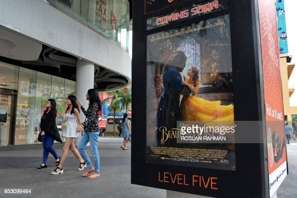 People walk past a poster for the film 'Beauty and the Beast' in Singapore on March 14 2017 The film has come under fire from religious figures in...