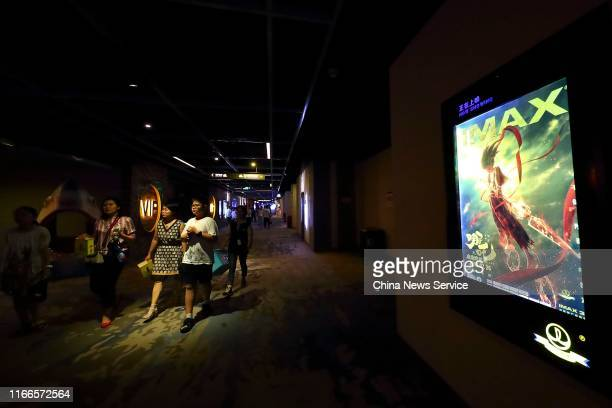 People walk past a poster of 3-D animation film 'Ne Zha' at a cinema on August 2, 2019 in Taiyuan, Shanxi Province of China. On August 7, the box...