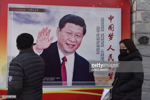 People walk past a poster of Chinese President Xi Jinping beside a street in Beijing on February 26 2018 Xi Jinping's tightening grip on China had...