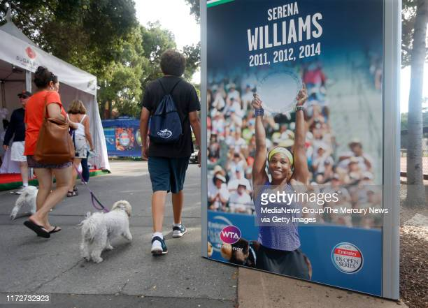 People walk past a poster of Serena Williams at the Bank of the West Classic tennis tournament at Taube Family Tennis Stadium at Stanford University...